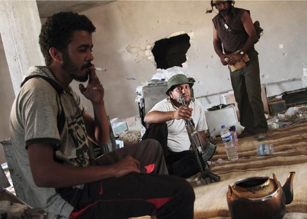 Rebeldes líbios descansam em casa na cidade de Kikla nesta segunda-feira - Crédito: Foto: AP