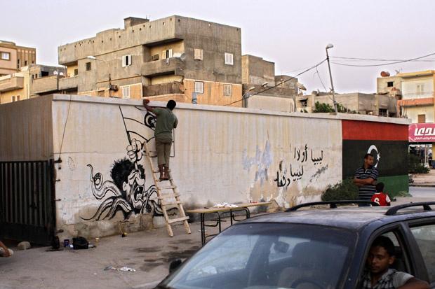 Artista pinta caricatura de Kadhafi em prédio de Benghazi, cidade-sede da rebelião, nesta quarta-feira - Crédito: Foto: AP