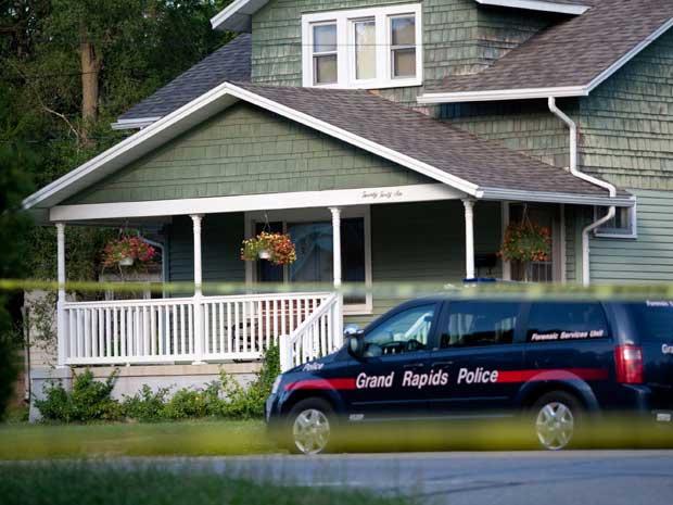 Polícia investiga uma das casas onde corpos foram encontrados em Grand Rapids. - Crédito: Foto: Adam Bird / AP Photo