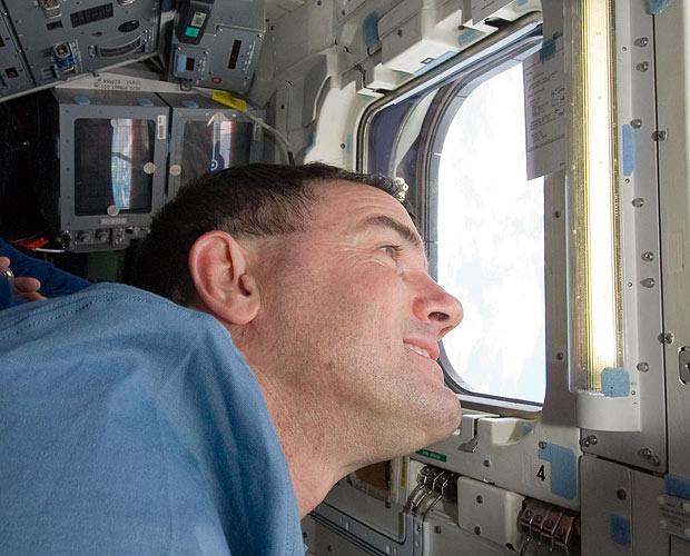 O astronauta Rex Walheim olha pela escotilha do Atlantis em direção à Terra - Crédito: Foto: Nasa