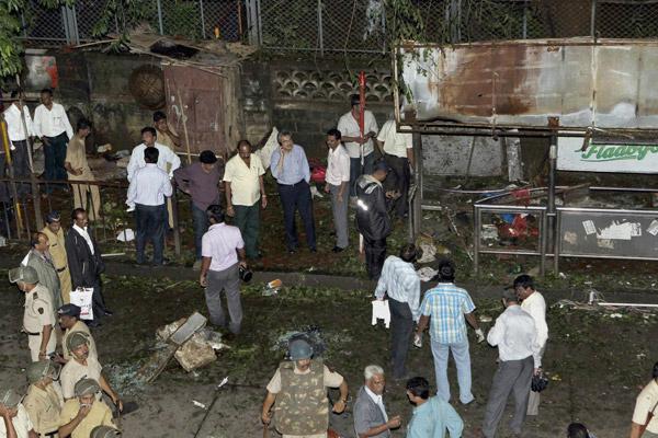 Policiais observam local de uma das explosões desta quarta-feira - Crédito: Foto: AP
