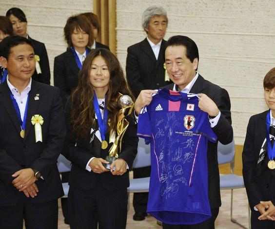 O primeiro-ministro Naoto Kan exibe orgulhoso a camisa da seleção japonesa autografada por jogadoras e comissão técnica. Ao seu lado direito estão o treinador Norio Sasaki e a capitã Homare Sawa, artilheira e eleita a melhor jogadora do Mundial. À esquerd - Crédito: Foto: Reuters