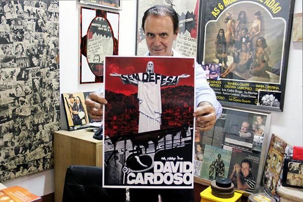 """Ator e diretor David Cardoso, em seu escritório, com modelo do cartaz do filme """"Sem Defesa"""". - Crédito: Foto: Renan Gonzaga"""