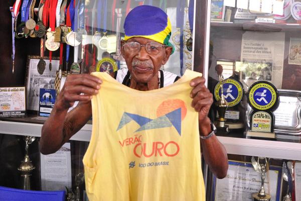Seo Paulino posou em frente à galeria que leva o nome dele, mostrando a camiseta que usou na primeira prova que disputou no ano de 1991 em Dourados, prova que incentivava largar o cigarro. - Crédito: Foto: Luiz Radai