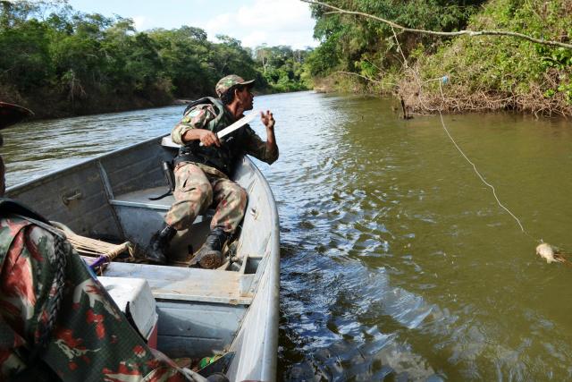 Agente da PMA tirando anzol de galho com peixe-capa fisgado; prática é uma das mais comuns nos rios. - Crédito: Foto: Divulgação/PMA