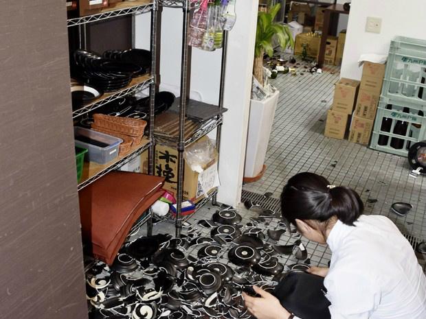 Funcionária recolhe louça quebrada que caiu de prateleira em um restaurante após um terremoto de 6,2 em Kumamoto, sul do Japão - Crédito: Foto: Kyodo News/AP