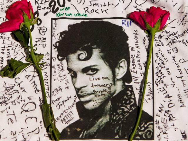 Flores são colocadas sobre uma camisa com mensagens escritas por fãs do cantor Prince em um memorial. - Crédito: Foto: Divulgação