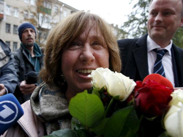 A escritora bielorrussa Svetlana Alexievich segura flores ao chegar para a entrevista coletiva, em Minsk. - Crédito: Foto: Vasily Fedosenko/Reuters