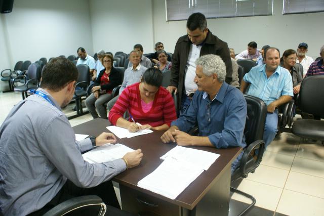 Prefeito Mário Valério testemunha assinatura de contrato de habitação feita por beneficiária do PNHR em Caarapó. - Crédito: Foto: Dilermano Alves
