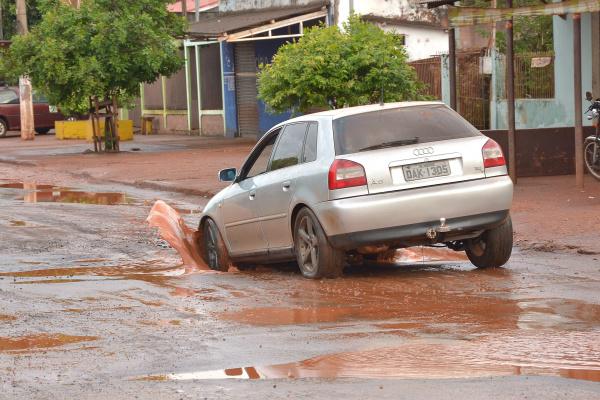 Veículos passam com dificuldade pelos buracos na Rua Neli Todeschini no Bairro Santa Maria -