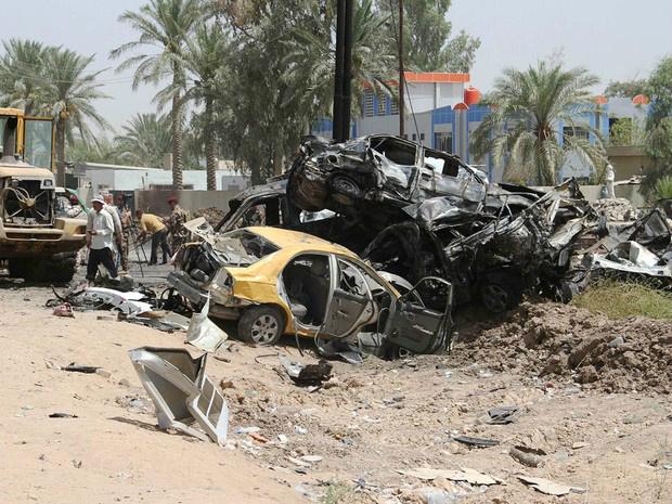 Moradores observam os destroços no local de uma explosão de ataque suicida na entrada da cidade de Al Khales, que fica 80 km a nordeste de Bagdá, no Iraque. Pelo menos dez pessoas morreram e 15 ficaram feridas no atentado   - Crédito: Foto: Younis Al-Bayati/AFP