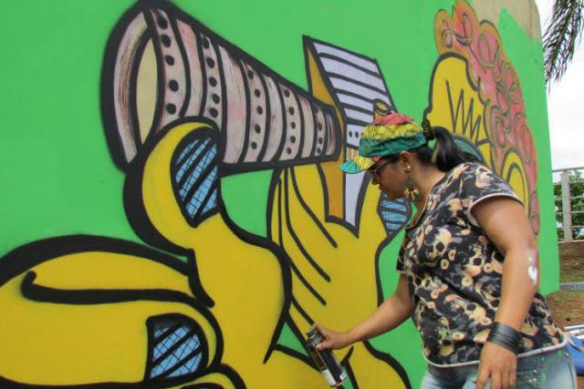 Artista plástica Marilena Grolli recupera grafite que embeleza parede de selaria na Orla Ferroviária de Campo Grande. - Crédito: Foto: Elvio Lopes