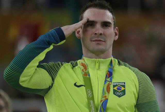 O ginasta Arthur Zanetti presta continência cerimônia após receber a medalha de prata no solo - Crédito: Foto: Julio Cortez/AP