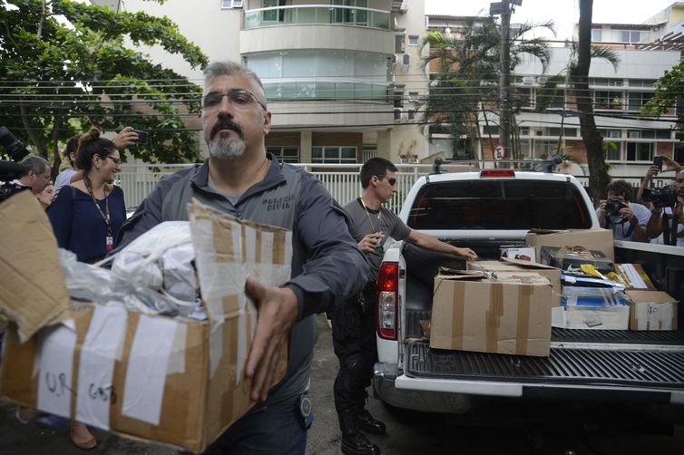 Policiais carregam caixas apreendidas em endereço ligado a suspeito de matar a vereadora Marielle Franco e o motorista Anderson Gomes - Crédito: Tânia Rêgo/Agência Brasil